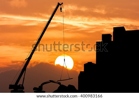 silhouette of excavator and crane working sunset background - stock photo
