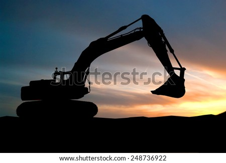 silhouette of Excavator loader at construction site with raised bucket over sunset  - stock photo