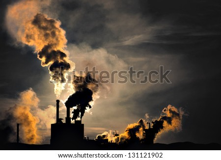 Silhouette of factory with chimneys and heavy smoke - stock photo