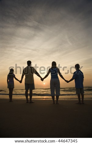 Silhouette of family holding hands on beach watching the sunset. Vertically framed shot. - stock photo
