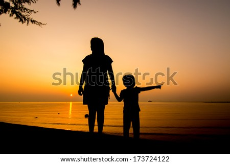 Silhouette of family on the beach at dusk.