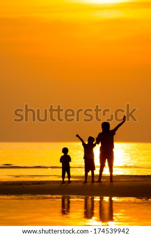 Silhouette of family on the beach during sunset.