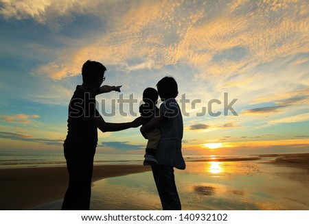 silhouette of family watching the sunrise on the beach - stock photo