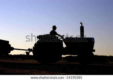 Silhouette of farmer on tractor with sun setting in background.