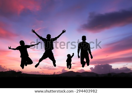 silhouette of father and boys jumping with joy at sunset