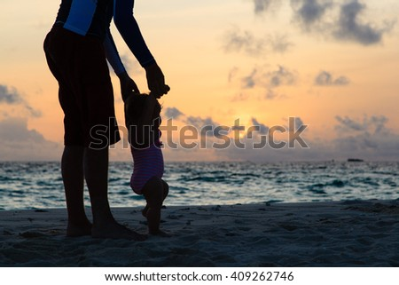 Silhouette of father and little daughter walking at sunset