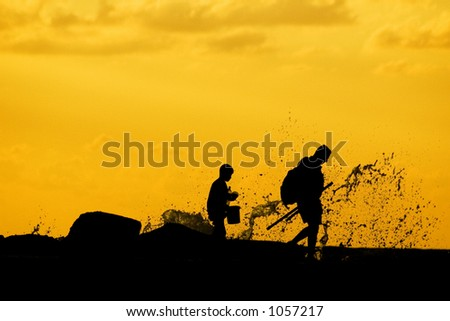 Silhouette of father and son going fishing and splashed by a wave