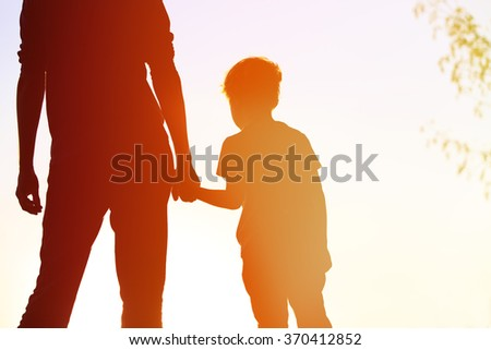 silhouette of father and son holding hands at sunset - stock photo