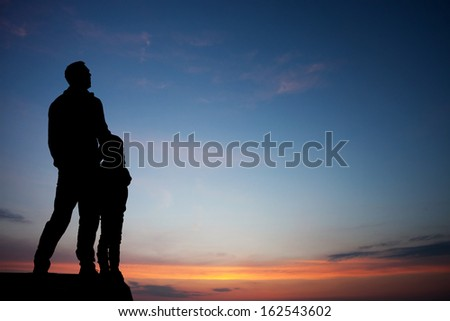silhouette of father and son in sunset sky  - stock photo