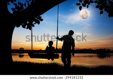 silhouette of father and son play swing under big tree the full moon background - stock photo