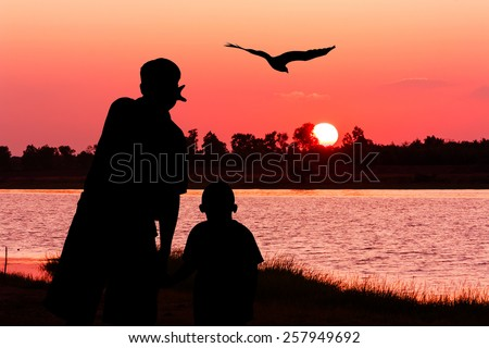 silhouette  of father and son point look at to eagle bird fly on the sky on the river sunset  - stock photo