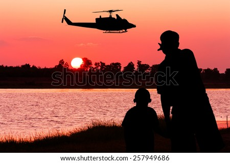 silhouette  of father and son point look at to helicopter on the sky on the river sunset  - stock photo