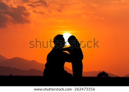 silhouette of Father kissing his son on the sunset background