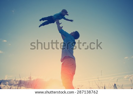 silhouette of father playing with his son in the park outdoors at sunset (intentional sun glare and vintage color) - stock photo