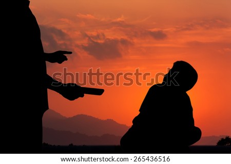 silhouette of father pointing finger at his son  and hand hold smart phone because he play smart phone long time. on sunset background - stock photo
