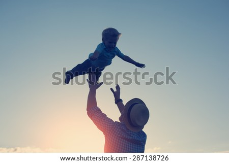 silhouette of father throwing up and catching his son in the park in the evening (intentional sun glare and vintage color, lens focus on father) - stock photo