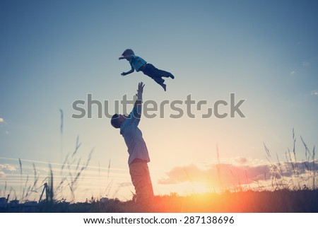 silhouette of father throwing up his son in the park at sunset (intentional sun glare and vintage color) - stock photo