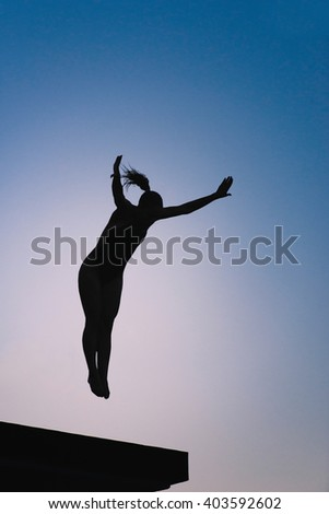 Silhouette of female diver jumping from platform