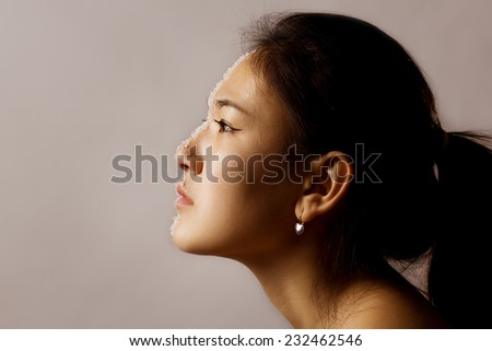 silhouette of female face with some detail still visible - stock photo