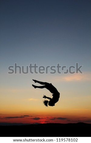 silhouette of female gymnast doing a somersault in sunset - stock photo