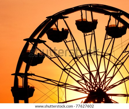 Silhouette of ferris wheel at sunset at county fair. - stock photo
