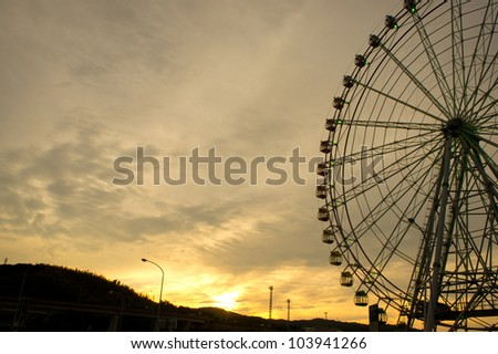 Silhouette of ferris wheel at sunset in japan.