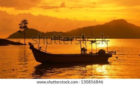 silhouette of fisherman boat in sunset at Perak, Malaysia. - stock photo