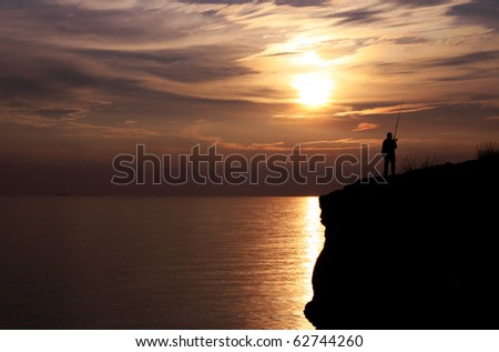 silhouette of fisherman fishing on a seaside cliff  during sunset - stock photo
