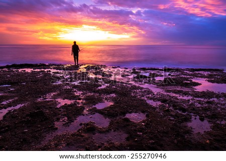 Silhouette of fisherman in amazing colorful sunset light, enjoying angling on beautiful coastline, recreation outdoors, favorite men's sport - stock photo