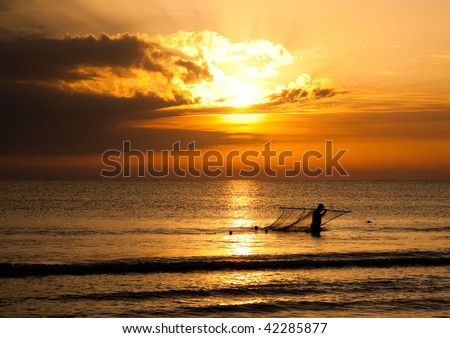 Silhouette Of Fisherman On The Sunrise Background - stock photo