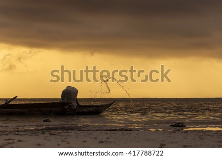 Silhouette of fisherman preparing for fishing at sunrise in Zanzibar, Tanzania - stock photo