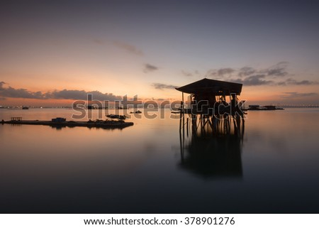 Silhouette of fisherman's wooden jetty during sunrise.  - stock photo