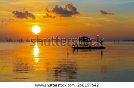 silhouette of fisherman with sunrise in the background - stock photo