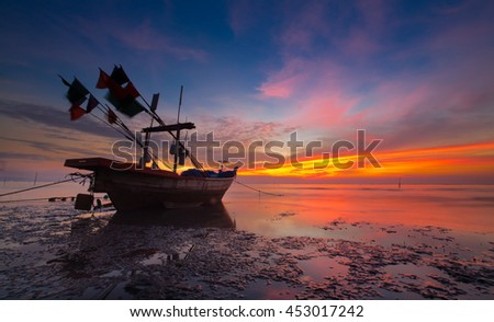silhouette of fishermen boat  with yellow and orange sunset - stock photo