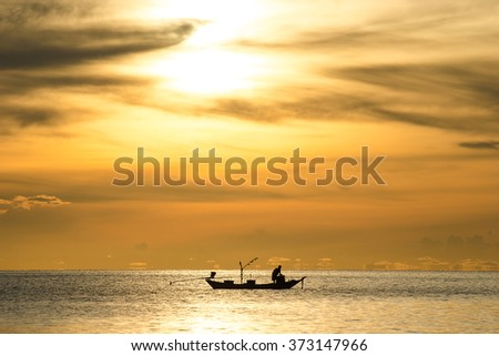 Silhouette of fishermen in the boat on sea with yellow and orange sun in the background, Thailand. - stock photo