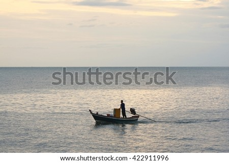 silhouette of fishermen on the sea and sky background - stock photo