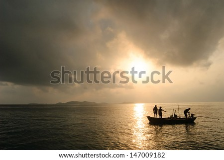 silhouette of fishermen with they boat