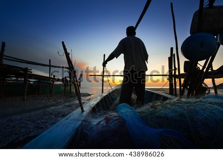 silhouette of fishermen with yellow and orange sun in the background  - stock photo