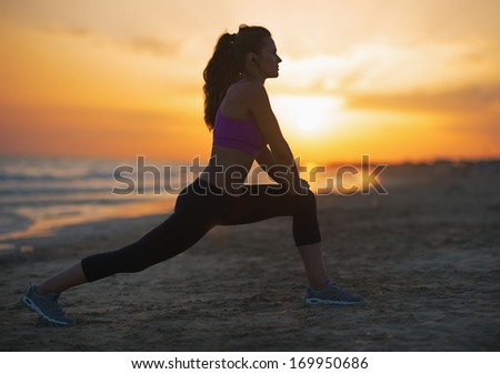 Silhouette of fitness young woman stretching on beach at dusk