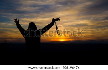 Silhouette of free and happy photographer with camera at sunset time on the mountain view. Freedom, success and triumph concept - stock photo