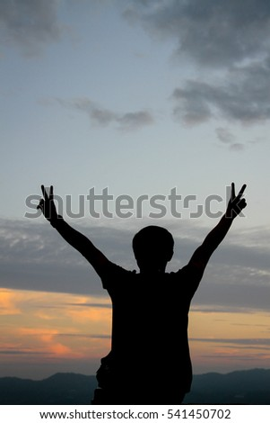 silhouette of free cheering man open arms at mountain peak