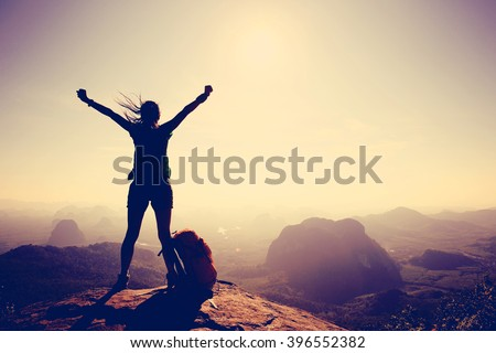 silhouette of free cheering woman hiker open arms at mountain peak - stock photo