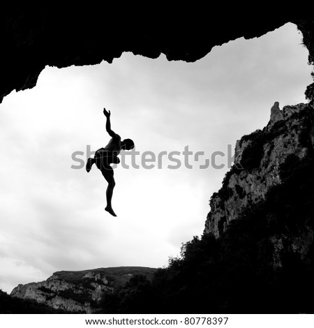 silhouette of freeclimber falling in water - stock photo