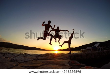 Silhouette of friends jumping at sunset on the beach - stock photo