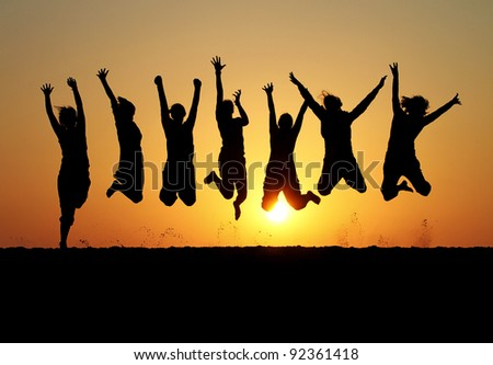 silhouette of friends jumping on beach during sunset time - stock photo