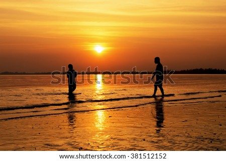 Silhouette of friends playing ball on the beach at sunset