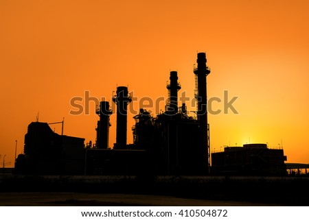 Silhouette of gas turbine electrical power plant at sunset