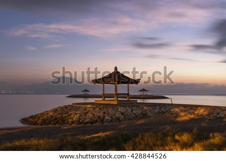 Silhouette of gazebos at Sanur beach against the morning twilight soft color sky.  Long exposure photography for colorful first day light serene seascape with Mount Agung at the background.