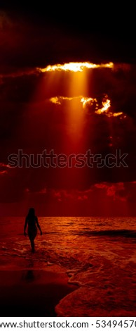 Silhouette of girl and dramatic dark red sky with sunbeam on background. - stock photo