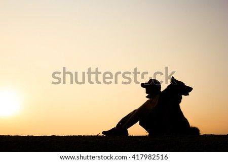 Silhouette of girl and her dog with beautiful sunset background.